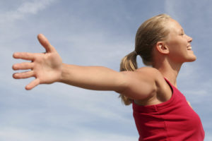 women stretching arms out in happiness